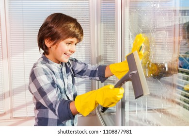 Boy cleaning windows with sponge and glass wiper