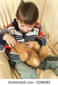 Boy cleans teeth his teddy bear