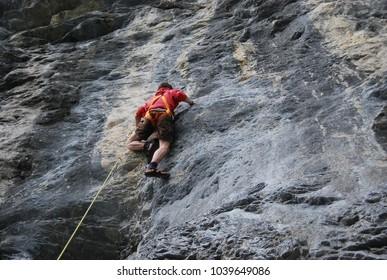 boy climbing activity grey rock