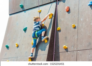 A boy in climbing equipment conquers the top of an artificial tower for climbers in a sports extreme recreation park.