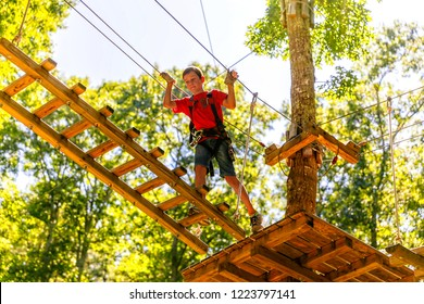 boy climbing in a high wire park above the ground. ziplining. the child on the zip line. The kid passes the rope obstacle course