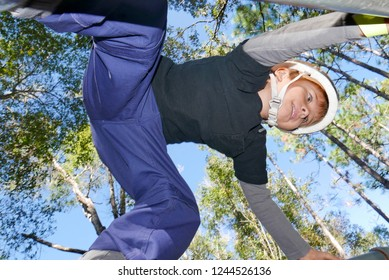 Boy climbing on bars on an obstacle course, viewed from below