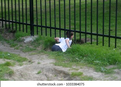 The boy is climbing under the fence. Summer background