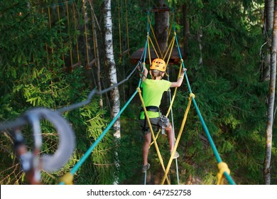boy climbs in a high wire park above the ground. ziplining. boy on the zip line. kid passes the rope obstacle course. back view