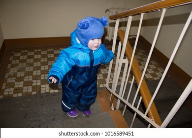 The boy climbs the stairs on the stairs himself