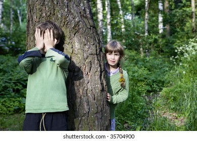 boy close his eyes by hand. Girl look out tree. Hide-and-seek