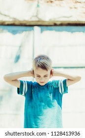 boy with closed ears in blue t-shirt