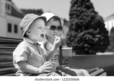 boy with closed eyes and sister enjoying ice cream on bench