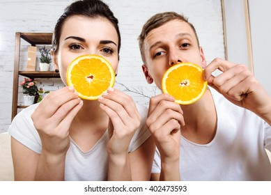 The boy closes eyes girl orange slices