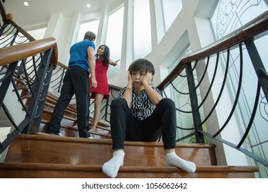 The boy is closing his ears between parents quarrel fighting. Stop violence concept.