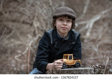 The boy in a coat and cap on the background of nature with a toy in the form of a car.