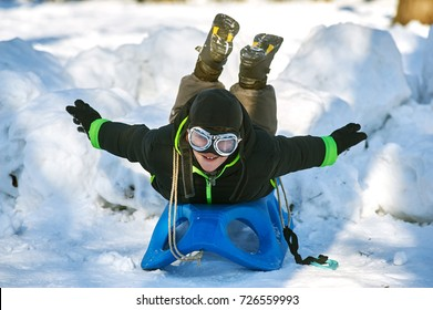 The boy in a cold winter day, a walk in the Park, holding the sled .Winter active holiday