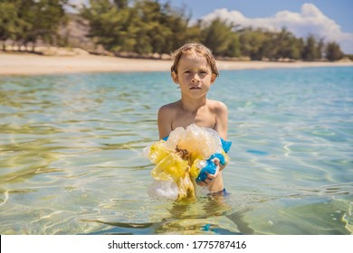 Boy collects packages from the beautiful turquoise sea. Paradise beach pollution. Problem of spilled rubbish trash garbage on the beach sand caused by man-made pollution and environmental, campaign
