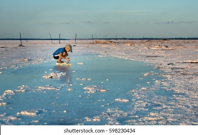 The boy collects salt crystals in salt-saturated water. Salt Plains National Wildlife Refuge, Oklahoma, US
