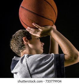 Boy concentrates, focuses as he shoots basketball - a foul shot perhaps