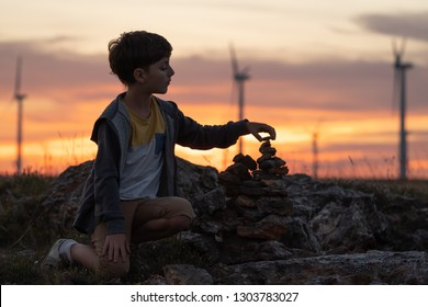 The boy is concentrating on building towers of stones against the backdrop of an orange sunset on a sunny day and wind turbines in a wind park on the seashore. Summer holidays. Relax