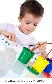 Boy concentrating at painting with watercolors - isolated