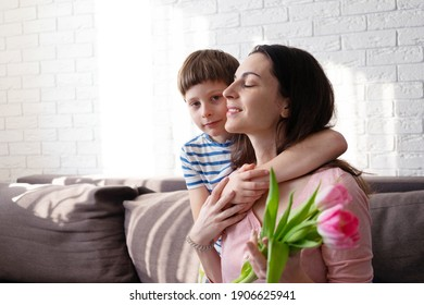 the boy congratulates his mother on March 8 and hugs her neck.