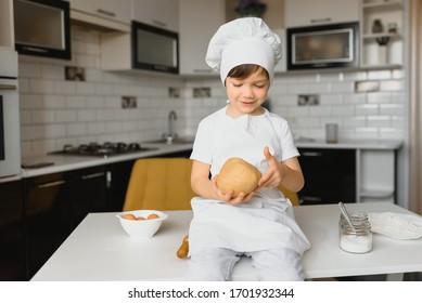 boy in cook hat sitting at a kitchen counter. Little boy in kitchen