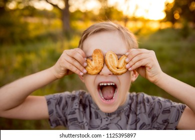 Boy with cookies. Cookies in the form of heart. A little blond boy eating a cookie. Funny boy with sweets at sunset