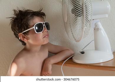 boy cools with a fan, portrait