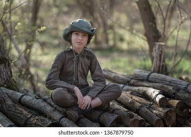 A boy in a coveralls and a hat sitting on a pile of sawn logs in the forest.