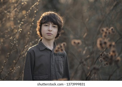 A boy in coveralls is standing in dry bushes of burdock.