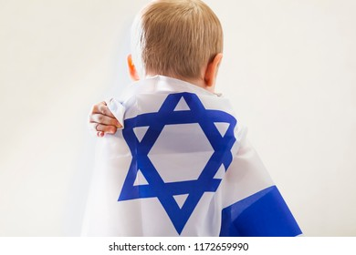 boy covered with the flag of Israel, rear view
