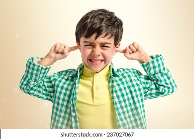 Boy covering his ears over ocher background.