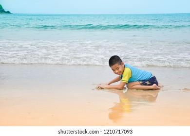 Boy crawls on the beach.