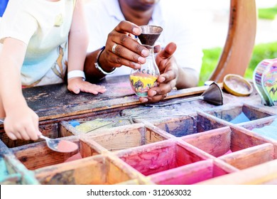 Boy creating colorful sand art filling a see-through container with assorted colored pigments at an outdoor display