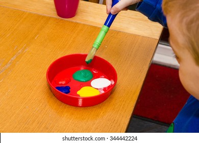 Boy creatively dips paint brush into red dish of paints on wooden table.