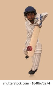 A boy in cricket uniform playing Cricket