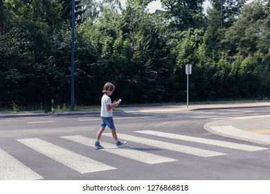 Boy crossing the street while looking at his smartphone