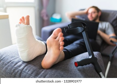 Boy with crutches and broken leg at home