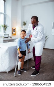 Boy with crutches. Caring dark-skinned pediatrician helping little boy to stand with crutches after breaking knee