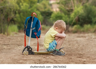 boy crying while sitting on the scooter on the background of summer green background