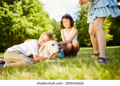 Boy cuddles with Golden Retriever in the park and hugs him