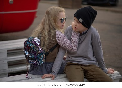 a boy and a curly haired blonde girl in sunglasses on a city street in the summer