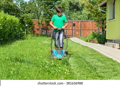 Boy cutting grass around the house in summertime - focusing on the operation