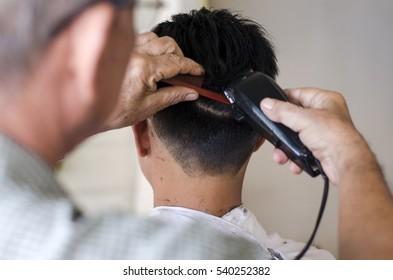 A boy was cutting hair at the barbershop, Thai school children