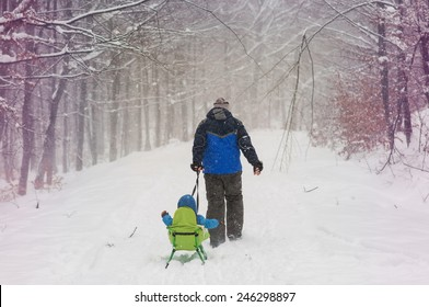 Boy and dad sledding in winter