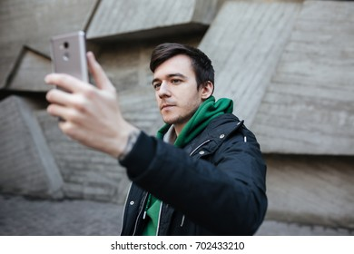 Boy with dark hair in black jacket standing on street with mobile phone in hand and making photo on front-camera. Portrait of young man in green sweatshirt thoughtfully looking in his cellphone