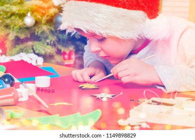 Boy decorating Christmas angel with yellow paint