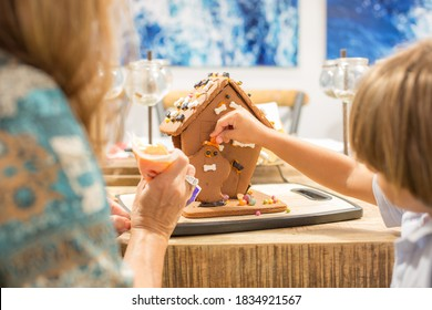 Boy decorating Halloween gingerbread house in the fall month of October using sweet candy ghost and bats in orange, black, and white plus orange icing and black frosting