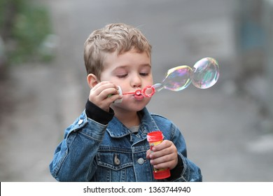 The boy in the denim jacket blows bubbles