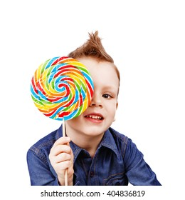 A boy in a denim shirt eating lollipop. Happy kid with a big candy isolated on white background