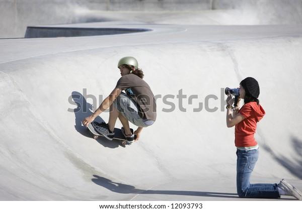 Boy dies tricks at the skateboard park as girl videotapes