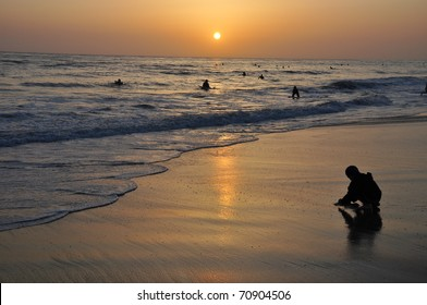 Boy digging in the sand at a Carlsbad California beach