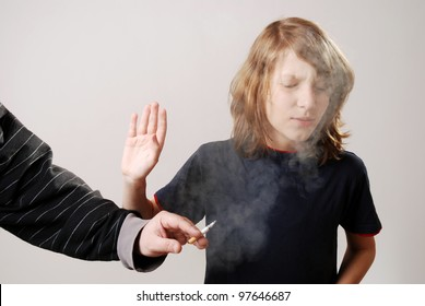 boy is disgusted by the smoke of a cigarette